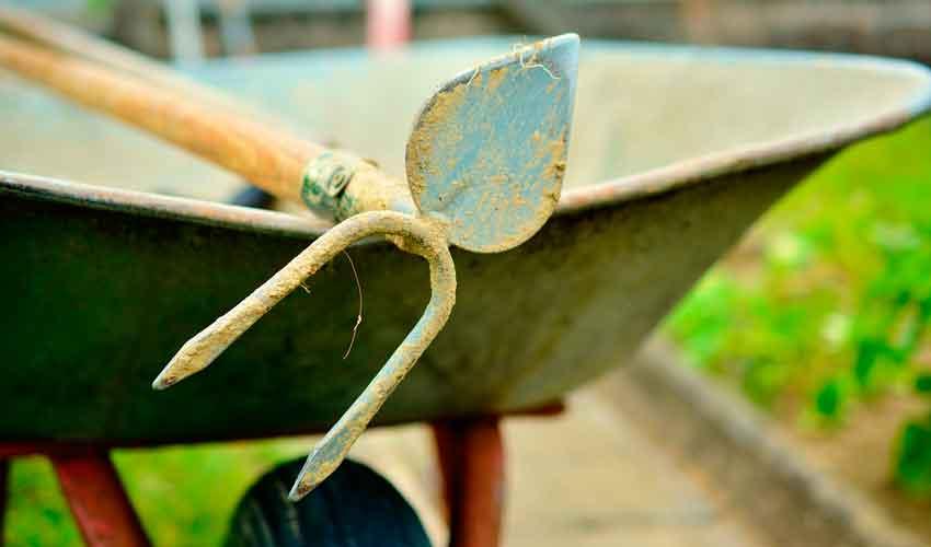 Gartenpflege mit Schubkarre und Hacke