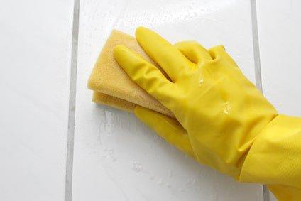 Gründliches Reinigen einer Fliese mit Schwamm