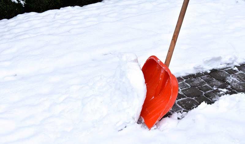 Gehweg wird mit Schneeschaufel geräumt