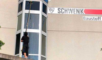 Gebäudereiniger reinigt Glasfassade mit Teleskopstange