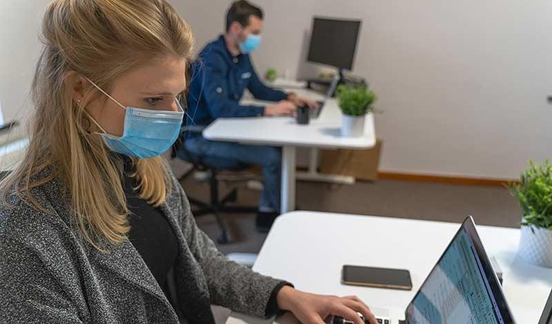 Büromitarbeiter mit Mundschutz an Schreibtischen